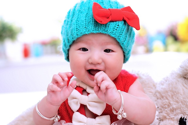 baby in blue hat with red bow