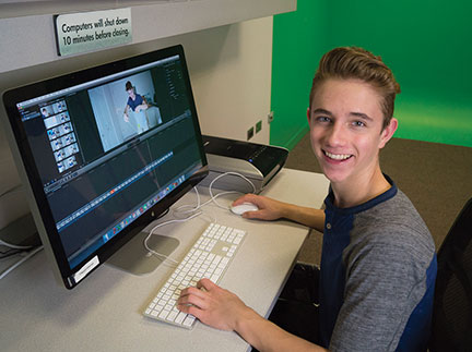 Photo of a teen using a computer in a digital media studio.