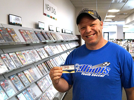 Photo of a man holding his Palatine Library card