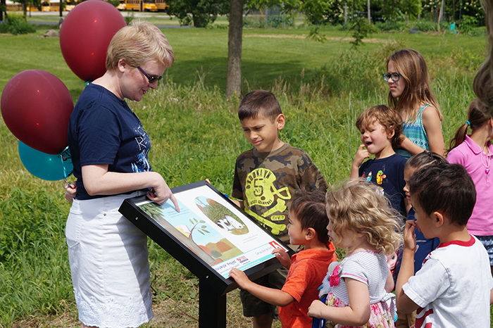 Executive Director Jeannie Dilger points to a picture on the StoryWalk as a group of children look on