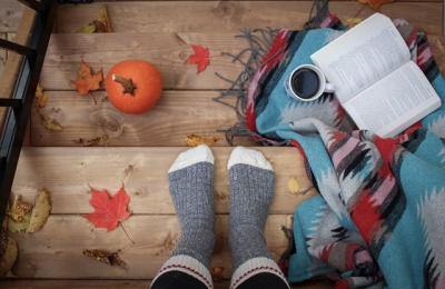 Photo of autumn leaves, pumpkin, coffee, and an open book on stairs