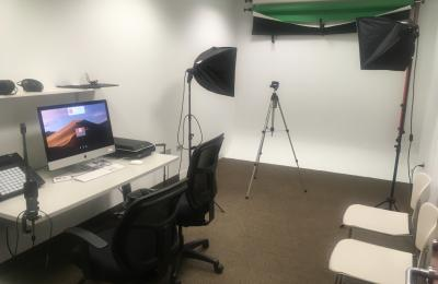 Inside shot of a Digital Media Studio with a computer, green screen, and lighting kit